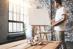 Man artist stands in front of a blank canvas on easel with palette in loft art studio. Male painter hold paintbrush in hand and mi Stock Image
