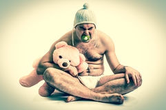 Man as baby. Child in diaper with pink teddy bear - retro style. Royalty Free Stock Photography
