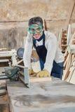 Man as carpenter with planing machine Royalty Free Stock Photos