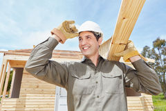 Man as construction worker building house. And carrying wood Stock Images