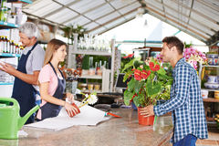Man as customer in nursery shop. Talking to women at checkout stock image