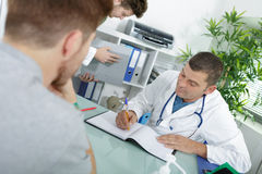 Man as doctor or physician during consultation at office. Man as doctor or physician during consultation at his office Royalty Free Stock Photo
