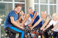 Man as fitness instructor in gym. Exercising with senior group in spinning class stock photography