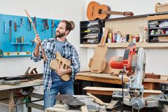 Guitar maker holding fingerboard and guitar body. Man as guitar maker holding fingerboard and guitar body at work stock photos
