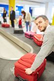 Man as a passenger on the luggage belt picks up suitcases royalty free stock photography