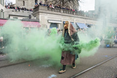Man as witch with green smoke-bomb at carnival stock photography