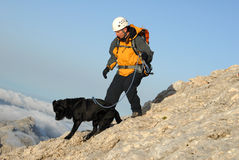 Man is ascending the mountain with his dog Royalty Free Stock Images