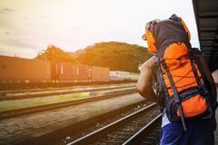 Man Asian backpack looking train at train station in Thailand. 1 Royalty Free Stock Photo