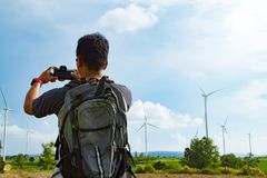 A man asian with backpack taking a photo on view of the wind turbine . stock photography