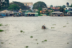 Man in asian conical hat is floating down Mekong river, Vietnam. Man in asian conical hat is floating down Mekong river on wooden boat, Can Tho Floating Market stock photos