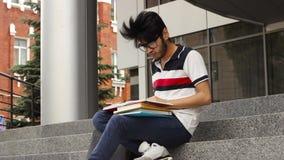 Man asiatiskt studentsammanträde på trappa och läseboken stock video