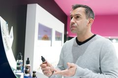 Man asking for refund in e-cigarette shop Stock Image