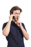 Man asking for silence with finger on lips while is calling on the phone Stock Photos