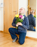 Man asks forgiveness with flowers. Marriage proposal. Adult man with flowers stock photo