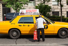 Man asks for information a taxi driver in Manhattan. NEW YORK CITY, NY, USA - JULY 07, 2015: A man asks for information a taxi driver in Manhattan. The taxicabs stock photography