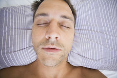 Man Asleep. With his head on a stripy pillow Stock Photo