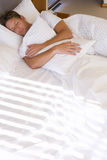 Man asleep in bed, hugging pillow, elevated view Stock Photo