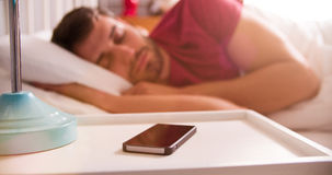 Man Asleep In Bed Using Alarm On Mobile Phone Royalty Free Stock Image