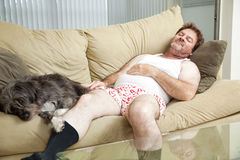Man Asleep with His Dog. Unshaven middle-aged man asleep on the couch with his dog Stock Photo