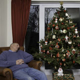 Man asleep next to Christmas Tree. Typical English Domestic Christmas Tree decorated with lights and baubles next to man asleep in leather arm chair Royalty Free Stock Photos