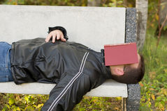 Man Asleep Outside. A man asleep outside with a book over his eyes Royalty Free Stock Photography