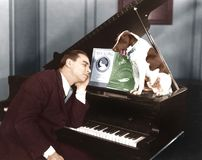 Man asleep at piano with dog Stock Image
