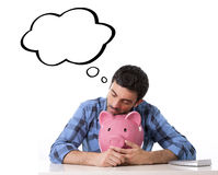Man asleep on pig piggy bank dreaming of being rich and buying new house or car royalty free stock photo