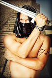 Man assassin with sexy torso. In black mask and hood holding  knife and sword in hands Stock Photos