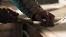 A man assembles furniture with hammer and nails stock video footage