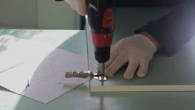 Man assembles furniture using a power screwdriver. Male worker assembles parts of furniture using a power screwdriver. Furniture assembly stock footage