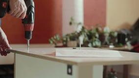 Man assembles furniture using a power screwdriver stock footage