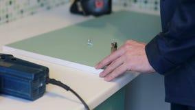 Man assembles furniture using a power screwdriver. Male worker assembles parts of furniture using a power screwdriver. Furniture assembly stock video