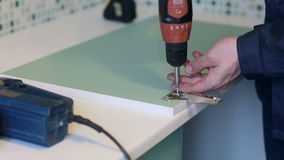 Man assembles furniture using a power screwdriver stock video footage