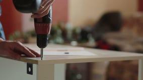 Man assembles furniture using a power screwdriver stock video