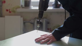 Man assembles furniture using a power screwdriver. Male worker assembles parts of furniture using a power screwdriver. Furniture assembly stock video footage