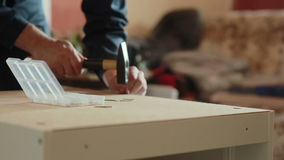 Man assembles parts of furniture using a hammer. stock video footage