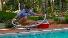Man assembles a pool vacuum cleaner. Providing service and maintenance of the pool. Cleaning the pool stock footage