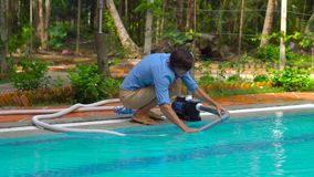 Man assembles a pool vacuum cleaner. Providing service and maintenance of the pool. Cleaning the pool stock video