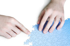 Man assembling blue puzzle Stock Photo