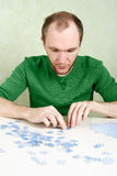 Man assembling blue puzzle pieces Royalty Free Stock Photos