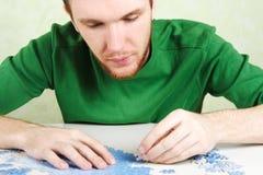 Man assembling blue puzzle pieces Stock Image