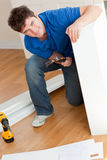 Man assembling furniture and holding a hammer Royalty Free Stock Photos