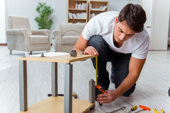 The man assembling furniture at home Stock Images
