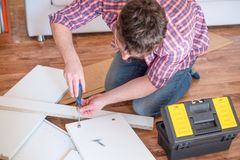 Man assembling furniture at home on the floor royalty free stock images