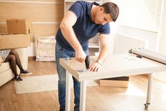 Man assembling furniture in their new flat. Man using tools stock photo