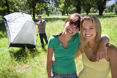 Man assembling grey dome tent in woodland clearing, focus on two young women with arms around each other, smiling, portrait Royalty Free Stock Images