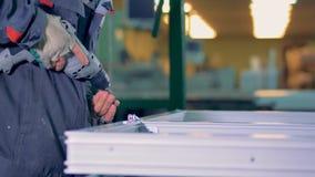 Man assembling plastic elements using industrial screwdriver. 4K stock footage