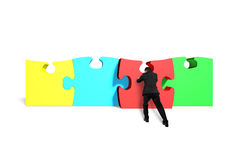 Man assembling puzzles. In white background Royalty Free Stock Photo