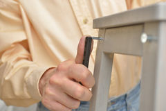 Man assembling the stool Stock Image