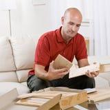 Man assembling wooden shelving parts. At home Stock Photos